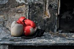 Weinlese-rote Boxhandschuhe auf alter Tabelle in gebranntem Raum lizenzfreie stockfotografie
