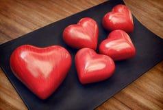 Weinlese roter hölzerner Valentine Hearts auf Brown Woody Table Lizenzfreie Stockbilder