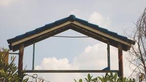 Weinlese Rusty Metal Gate mit blauem Ziegeldach stockfoto