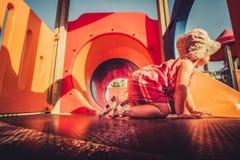 Weinlese schoss vom Babyprofil, das innerhalb des orange Spielplatzstruktur-Kindergesichtspunkts kriecht Stockbilder