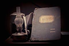 Weinlese-Stillleben mit einer Lampe und einer Buchhaltungszeitschrift Lizenzfreies Stockfoto