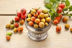 Weinlese streifte Kasten Hagebuttefrüchte auf Holztisch Lizenzfreie Stockfotos