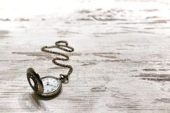Weinlese-Taschen-Uhr auf altem gealtertem hölzernem Hintergrund Lizenzfreie Stockbilder