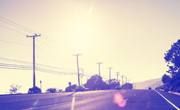 Weinlese tonte Landstraße bei Sonnenuntergang Lizenzfreie Stockbilder