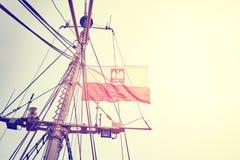 Weinlese tonte polnische Flagge auf einem Fahnenmast bei Sonnenuntergang Stockfotografie