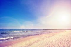 Weinlese tonte Strand bei Sonnenuntergang mit Blendenfleckeffekt Lizenzfreie Stockfotografie