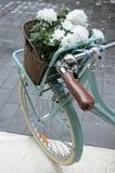Weinlese-Türkisfahrrad mit einem Behälter von weißen Blumen Stockfoto