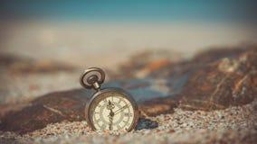 Weinlese-Uhr auf Sand-Strand stockfotografie