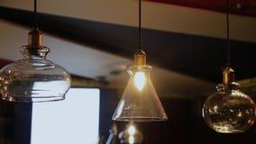 Weinlese und Retro- gelbe Glühlampe, die über dunklem Hintergrund im Café nachts hängen Viel helle Luxuslampe dekorativ stock footage