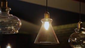 Weinlese und Retro- gelbe Glühlampe, die über dunklem Hintergrund im Café nachts hängen Viel helle Luxuslampe dekorativ stock video footage
