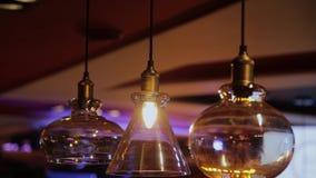 Weinlese und Retro- gelbe Glühlampe, die über dunklem Hintergrund im Café nachts hängen Viel helle Luxuslampe dekorativ stock video