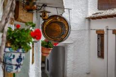Weinlese und rundes Holzschild, die an einer Straße eines Dorfs hängen Stockbild