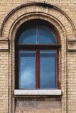 Weinlese wölbte Fenster in der Wand des gelben Ziegelsteines Schwarzes Glas in einem kastanienbraunen dunkelroten Holzrahmen Das  stockfotografie