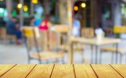 Weinlese, Weichzeichnungsholztisch mit Unschärfekaffeestube Hintergrund lizenzfreies stockbild