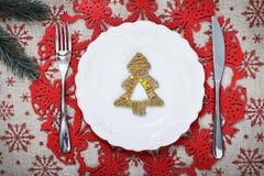 Weinlese-Weihnachtsplatte auf Feiertagshintergrund mit Weihnachtsbaum Segeltuchhintergrund mit roten Funkelnschneeflocken Abbildu Stockbild