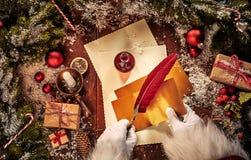 Weinlese-Weihnachtsszene mit Santa Claus, die einen Brief mit einem Federfederkiel und Dekorationen auf eine rustikale Tabelle mi lizenzfreie stockfotografie