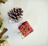 Weinlese-Weihnachtsverzierung mit Goldband, rotem Geschenk und Kiefernkegel Lizenzfreies Stockbild