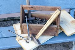 Weinlese-Werkzeugkasten mit Werkzeugen Alte Holzkiste mit Gebäudewerkzeugen, Bretter für Reparatur auf einer Holzbank Stockfoto