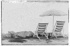 Weinleseart filterte Bild von zwei leeren Strandstühlen und -regenschirm auf Küstenlinie stockfoto