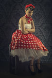 Weinleseart - Frau, die im Raum mit rotem Tupfenkleid sitzt Stockbild