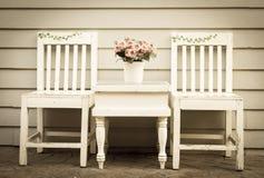 Weinleseartfarbe des Stuhls und der Tabelle mit Blumenvase. Stockfotografie