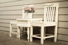 Weinleseartfarbe des Stuhls und der Tabelle mit Blumenvase. Stockbilder