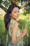 Weinleseartfoto eines jungen Mädchens, das Kleeblumenstrauß hält Lizenzfreie Stockbilder