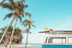 Weinleseauto parkte auf der tropischen Strandküste mit einem Surfbrett auf dem Dach Lizenzfreies Stockfoto