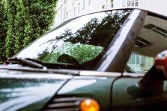 Weinleseautodetail, Konzept des britischen Patriotismus gezeigt als Flagge auf Spiegel, Bäume in der Reflexionswindschutzscheibe, lizenzfreie stockfotos