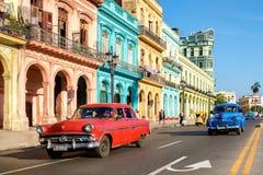 Weinleseautos und bunte Gebäude in altem Havana Stockbild