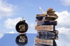 Weinlesebücher und alte Borduhr auf Spiegel Lizenzfreie Stockfotografie
