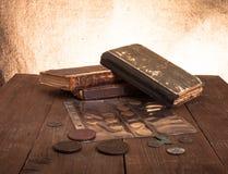 Weinlesebücher und -münzen auf altem Holztisch Stockbild