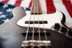 Weinlesebass-Gitarre auf Hintergrund der amerikanischen Flagge Stockfotos