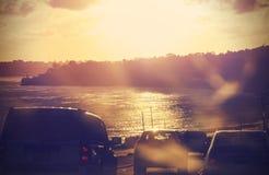 Weinlesebild der Straße mit Autos in der Bewegung, blured gegen Sonne Stockbild