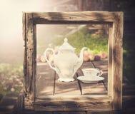 Weinlesebild des Teesatzes im Garten im Holzrahmen Stockfotos