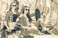 Weinlesebild von jungen schönen Mädchen mit Skateboard, im Freien stockbild