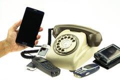 Weinlesebildart des neuen intelligenten Telefons mit altem Telefon auf weißem Hintergrund Neue Kommunikationstechnologie Stockfotografie