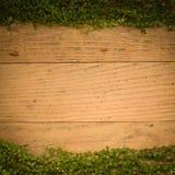 Weinlesebretterboden-Beschaffenheitshintergrund mit grünen Blättern Stockfotografie