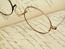 Weinlesebrillen auf einem handgeschriebenen Tagebuch Lizenzfreie Stockfotografie