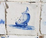 Weinlesedelft-blaue Fliese mit holländischer Segelnlieferung Stockfotos