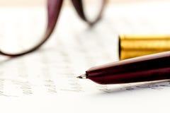 Weinlesefüllfederhalter auf einem Buchstaben, Gläser hinten stockfoto