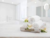 Weinlesefach, Badekurorttücher und Orchideenblumen über unscharfem Badezimmer Stockfotografie