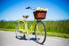 Weinlesefahrrad mit Weidenkorb und Blumen in der Landschaft Stockfotos