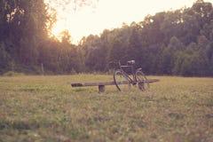Weinlesefahrrad und alte Bank Stockfoto