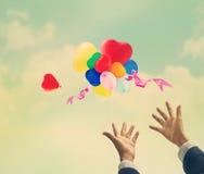 Weinlesefarbton, Herzformballon bunt und vibrierend auf Wolkenhimmel des Sommertages Stockbilder