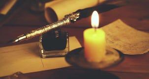 Weinlesefederkiel und -tintenfaß auf braunem Holztisch mit Kerze stock footage