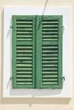 Weinlesefenster mit Fensterläden über weißer Wand Stockfotografie