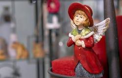 Weinlesefigürchen eines Mädchens in einem roten Mantel mit Engelsflügeln stockfotografie