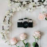 Weinlesefilmkamera in der Mitte, Kirschblüte-Niederlassung, Rosarose blüht auf dem weißen hölzernen Schreibtisch Draufsicht, flac Stockfotos