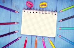 Weinlesefoto, bunte Zeichenstifte, Bleistiftspitzer und Notizblock auf Brettern, Schulzubehör, Kopienraum für Text Lizenzfreie Stockfotos
